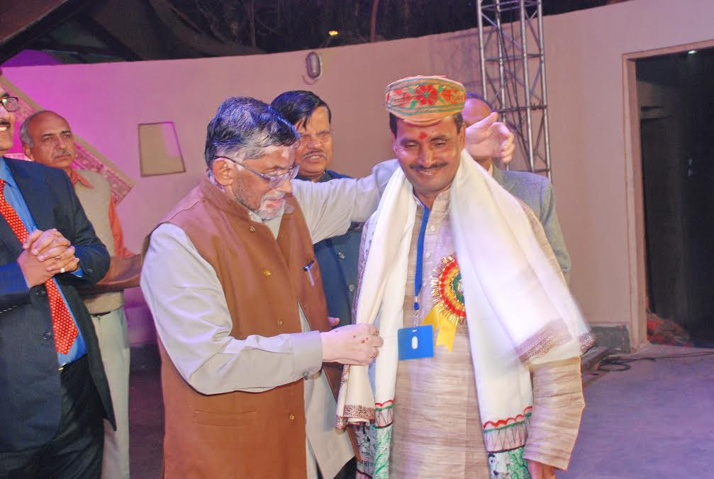 Devendra Kumar Jha receives shawl from minister of state