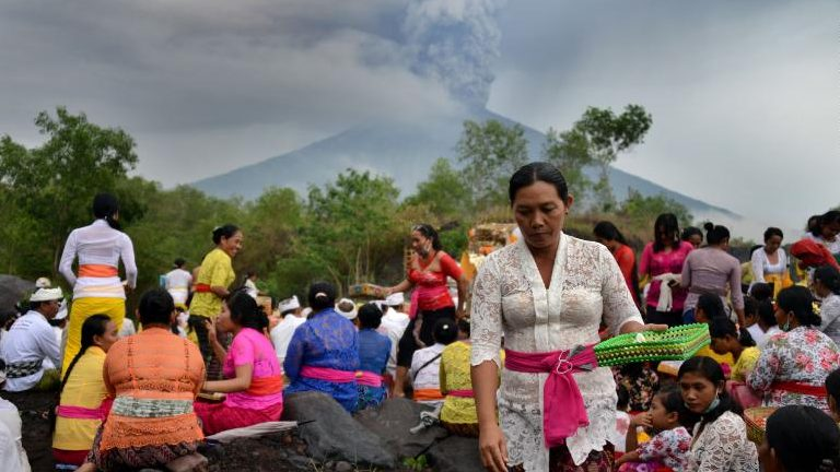 Balinese Hindus take part in a ceremony, where they pray near Mount Agung in hope of preventing a volcanic eruption, in Muntig village of the Kubu sub-district in Karangasem Regency on Indonesia's resort island of Bali on November 26, 2017. A volcano on the Indonesian tourist island of Bali sent plumes of grey smoke and steam thousands of metres into the air on November 26 for the third day in a week, triggering flight cancellations which have left thousands of tourists stranded, officials said Sunday. / AFP PHOTO / SONNY TUMBELAKA